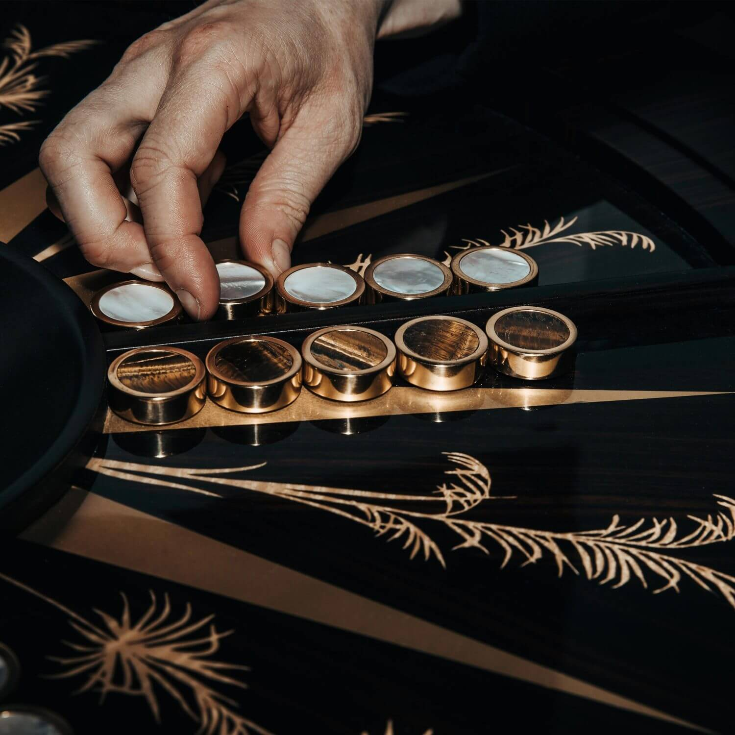 A man playing backgammon with semi-precious stone playing pieces