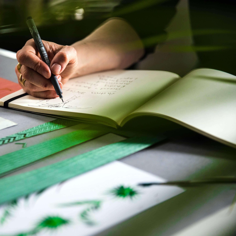 Alexandra Llewellyn sketching palm leaf designs in her sketchbook
